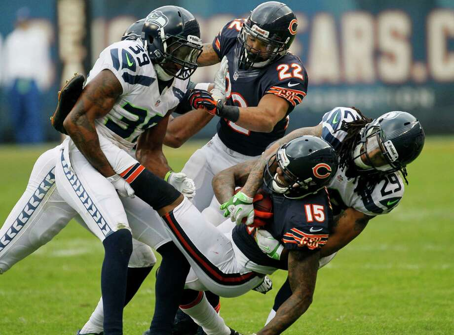 Chicago Bears wide receiver Brandon Marshall (15) is tackled by Seattle Seahawks cornerback Brandon Browner (39) and safety Earl Thomas (29) in the first half of an NFL football game in Chicago, Sunday, Dec. 2, 2012. Photo: AP