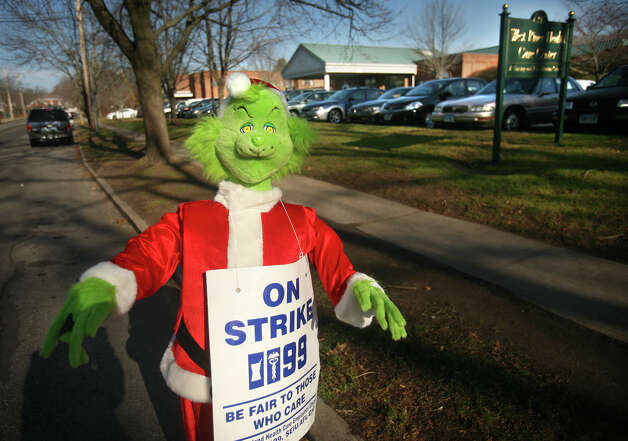 A Grinch dressed in a Santa suit placed by SEIU 199 union strikers stands for the second consecutive year outside West River Health Care Center on Orange Avenue in Milford on Thursday, November 29, 2012. Photo: Brian A. Pounds / Connecticut Post