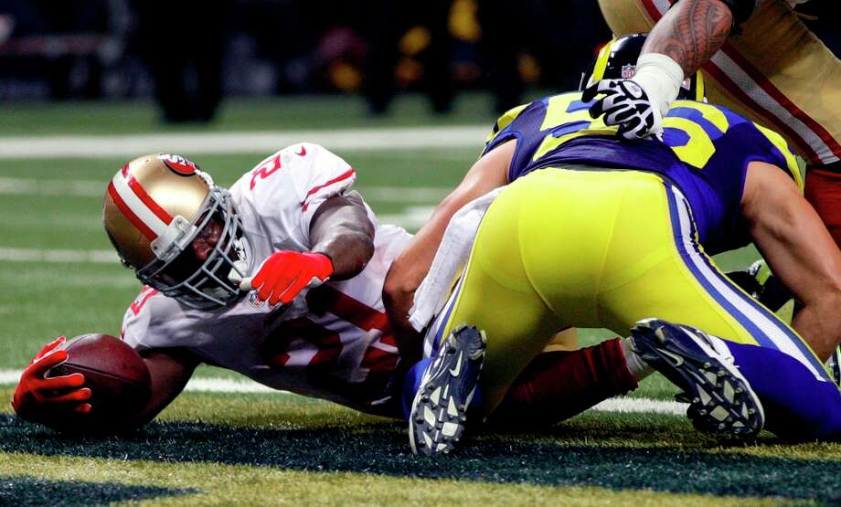 San Francisco 49ers running back Frank Gore, left, scores on a 1-yard run past St. Louis Rams linebacker Josh Hull during the first quarter of an NFL football game on Sunday, Dec. 2, 2012, in St. Louis. Photo: Tom Gannam, Associated Press / FR45452 AP