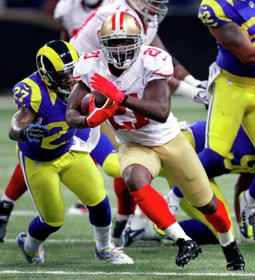 San Francisco 49ers running back Frank Gore (21) gets past St. Louis Rams free safety Quintin Mikell on his way to a 23-yard gain during the first quarter of an NFL football game on Sunday, Dec. 2, 2012, in St. Louis. Photo: Tom Gannam, Associated Press / FR45452 AP