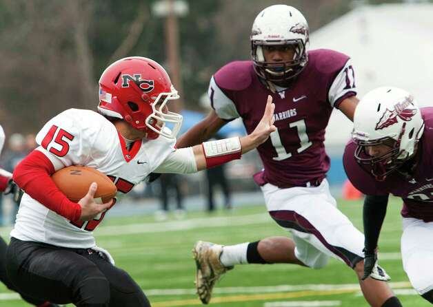 New Canaan high school quarterback Nick Cascione runs into a couple of  Windsor high school defensemen in the CIAC class L semifinal football tournament game played at Bunnell high school, Stratford, CT on Sunday December 2nd, 2012. Photo: Mark Conrad / Stamford Advocate Freelance
