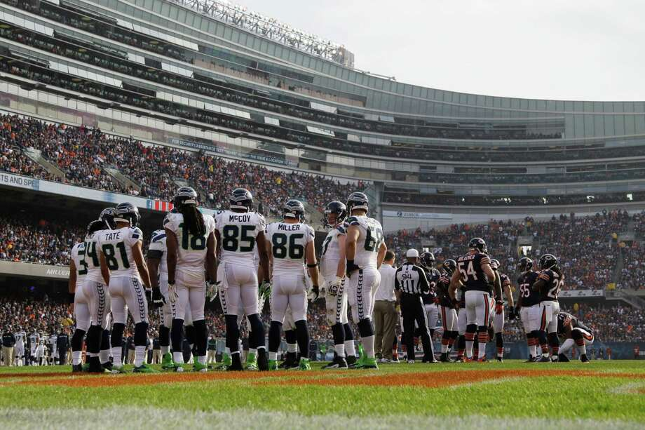 The Seattle Seahawks and Chicago Bears huddle before a playin the first half of an NFL football game in Chicago, Sunday, Dec. 2, 2012. Photo: AP