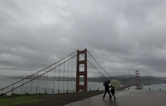 A man and woman walk along a vista point looking toward the Golden Gate Bridge and San Francisco from the Marin Headlands in Marin County, Calif., Thursday, Nov. 29, 2012. The National Weather Service says that by late morning Thursday 1 inch of rain had fallen in several hours across the western side of the county. Much of Northern California is under a variety of warnings and advisories for rain, snow and high winds. (AP Photo/Jeff Chiu) Photo: Jeff Chiu, Associated Press