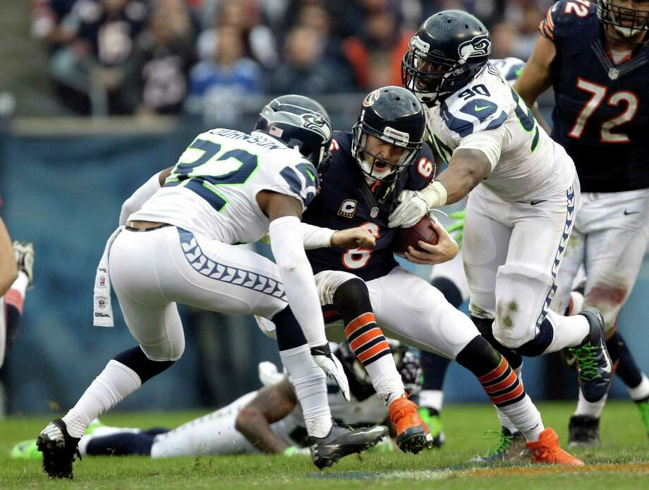 Chicago Bears quarterback Jay Cutler (6) is tackled by Seattle Seahawks safety Jeron Johnson (32) and defensive end Jason Jones (90) during the second half of an NFL football game in Chicago, Sunday, Dec. 2, 2012. Photo: AP