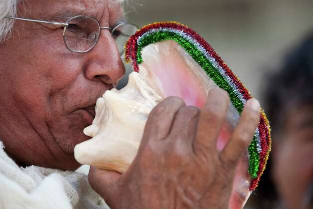"Pablo Muñoz blows a conch before a parade Dec. 2, 2012 in Houston. in an expression of devotion and thanks-giving to  Guadalupe, the Patroness of the Americas, matachines dance and celebrate, and march Dec. 2, 2012 in Houston through the streets of downtown. Now in its 37th year, this is the annual city-wide celebration of the Feast of Our Lady of Guadalupe. The day unites people from across the Archdiocese of Galveston-Houston as thousands come together to rejoice. The event began at noon with a procession from 1700 San Jacinto to the George R. Brown Convention Center. Matachines are indigenous folk dance troupes, mariachis and other singers. The matachines wear elaborate headpieces and traditional Aztec-style dress.  From a press release: ""This celebration in the Hispanic Catholic community means being able to maintain a cultural heritage that derives almost 5 centuries,"" said Gilberto Heredia, president of the Guadalupana Association.  The general community is invited to this annual event.  The event is sponsored by the Guadalupana Association of the Archdiocese of Galveston-Houston. It commemorates the official Church feast day of Our Lady of Guadalupe on December 12. On a hill near a rural village just outside of Mexico City, the Virgin Mary, Our Lady of Guadalupe, appeared to a humble peasant named Juan Diego, now St. Juan Diego. Surrounded by light and speaking in his indigenous tongue of Nahuatl, Our Lady told Juan Diego she wanted a church built to manifest her Son's love and hear the petitions of the faithful. To help him in his mission, she gave him a sign, imprinting her beautiful image on his cloak. From it would flow miracles. The news spread quickly throughout Mexico, and in the following years, millions would convert to Catholicism. The Archdiocese of Galveston-Houston serves 1.2 million Catholics in 10 counties. It is the largest Roman Catholic diocese in Texas and the 12th largest in the United States. Photo: Eric Kayne / © 2012 Eric Kayne"