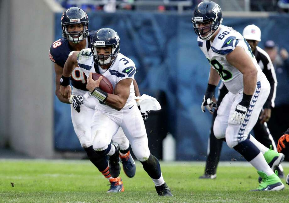 Seattle Seahawks quarterback Russell Wilson (3) rushes past Chicago Bears defensive end Corey Wootton (98) during the second half of an NFL football game in Chicago, Sunday, Dec. 2, 2012. Photo: AP