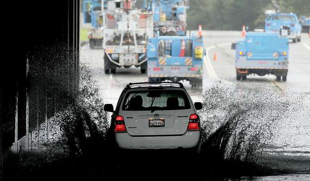 A vehicle transits a flooded underpass in San Rafael, Calif., on Sunday, Dec. 2, 2012, as utility workers work to repair a downed power line. Although sunny skies reappeared throughout the region Sunday afternoon, flood warnings remain for several rivers. (AP Photo/Noah Berger) Photo: Noah Berger, Associated Press