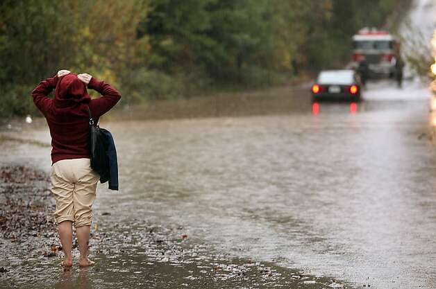 Kimberly Masklyne looks at her flooded car, Sunday Dec. 2, 2012, in Windsor, Calif. The National Weather Service issued flood warnings yesterday for both the Napa and Russian rivers. (AP Photo/The Press Democrat, Kent Porter) Photo: Kent Porter, Associated Press