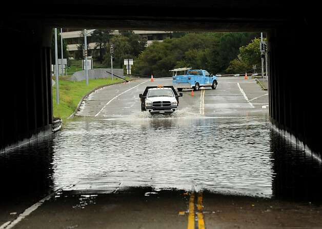 A traffic control vehicle transits a flooded underpass in San Rafael, Calif., on Sunday, Dec. 2, 2012. Days of heavy rains have left the region saturated and several rivers are expected to flood their banks Sunday afternoon. (AP Photo/Noah Berger) Photo: Noah Berger, Associated Press