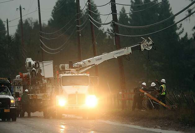 Utility crews work in the wind and rain to repair a power pole that was damaged by the overnight storm along Hall Road in Santa Rosa, Calif., on Sunday, Dec. 2, 2012. The National Weather Service issued flood warnings yesterday for both the Napa and Russian rivers. Photo: Kent Porter, Associated Press