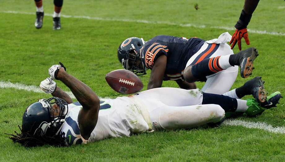 Seattle Seahawks wide receiver Sidney Rice, left, lies on the field after a hard hit by Chicago Bears safety Major Wright on his game-winning touchdown reception in overtime of an NFL football game in Chicago, Sunday, Dec. 2, 2012. The Seahawks won  23-17. Photo: AP