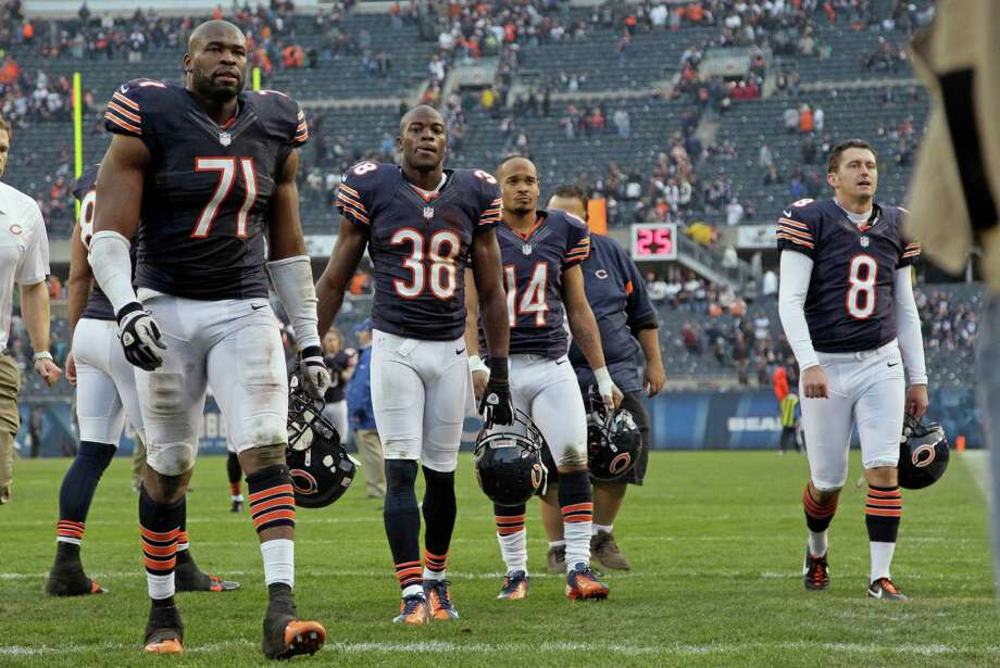 Chicago Bears players Israel Idonije (71), Zack Bowman (38), Eric Weems (14) and Adam Podlesh (8) walk off the field after the Bears' 23-17 loss in overtime to the Seattle Seahawks in an NFL football game in Chicago, Sunday, Dec. 2, 2012. Photo: AP
