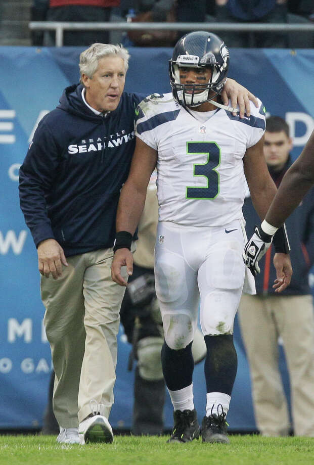Seattle Seahawks head coach Pete Carroll walks off the field with quarterback Russell Wilson (3) after the Seahawks' 23-17 win in overtime over the Chicago Bears in an NFL football game in Chicago, Sunday, Dec. 2, 2012. Photo: AP