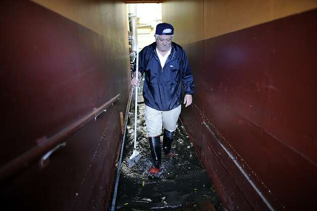 Building manager Sam Piccazo wades through water in his apartment building that was over knee deep earlier this morning.  Business on the 2100 block of Folsom St. in San Francisco were flooded this morning by water that backed up through the sewage lines.  Sunday December 2nd, 2012. Photo: Michael Short, Special To The Chronicle
