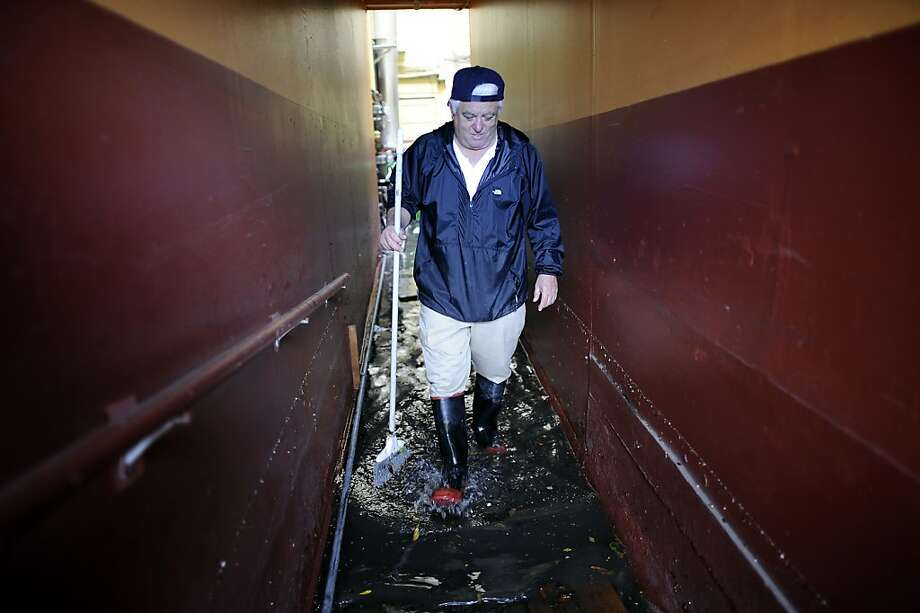 Building manager Sam Piccazo wades through water in his apartment building that was over knee deep earlier this morning.  Business on the 2100 block of Folsom St. in San Francisco were flooded by water that backed up through the sewage lines.  Sunday December 2nd, 2012. Photo: Michael Short, Special To The Chronicle