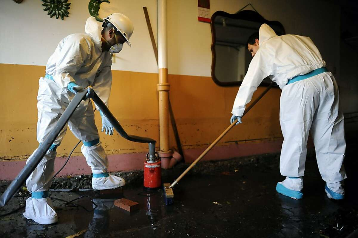 Workers from Servicemaster Restoration Services pump out standing water from the garage of an apartment building on Folsom St. Business on the 2100 block of Folsom St. in San Francisco were flooded by water that backed up through the sewage lines on Sunday December 2nd, 2012.