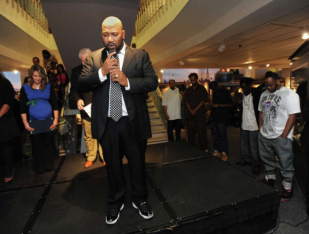 Bernard 'Bun B' Freeman offers an opening prayer Sunday at the unveiling of the UGK exhibit at the Museum of the Gulf Coast. Fans of the Underground Kings gathered at the event to see the rap star and the exhibit.  Photo taken Sunday, December 02, 2012 Guiseppe Barranco/The Enterprise Photo: Guiseppe Barranco, STAFF PHOTOGRAPHER / The Beaumont Enterprise