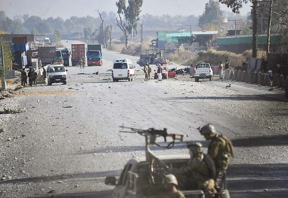 After a predawn assault by Taliban suicide bombers failed to breach the base, Afghan security forces block the road. Photo: Nasrullah Khan, Associated Press