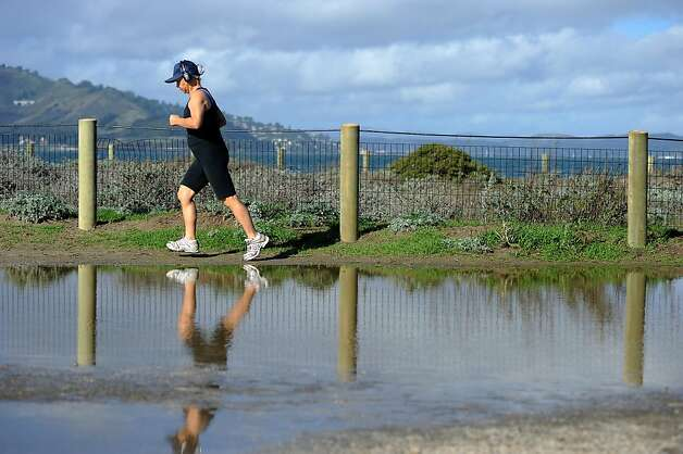 A runner at Crissy Field taking advantage of a sunny break in the storm in the middle of the day avoids a large puddle. Photo: Michael Short, Special To The Chronicle