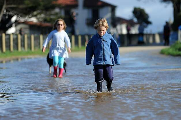 Charlie Adams, 5, and his sister Alice, 7, wade through a pool of water left by the storm at Crissy Field. Photo: Michael Short, Special To The Chronicle