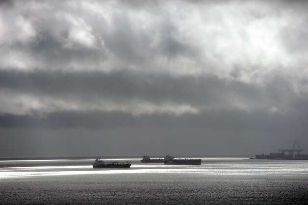 Container ships sit in the Bay as dark clowds pass over head.  A series of storms passed through the Bay Area on Sunday December 2nd, 2012, dumping rain accompanied by high winds. Photo: Michael Short, Special To The Chronicle