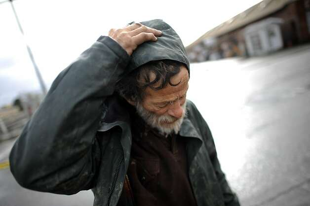 Ivan Cox, who has been homeless for 15 years, struggles to stay dry as he walks down High St. in Oakland, CA.  High St. near the 880 freeway in Oakland is seen partially under water after heavy rains during the morning of Sunday December 2nd, 2012. Photo: Michael Short, Special To The Chronicle