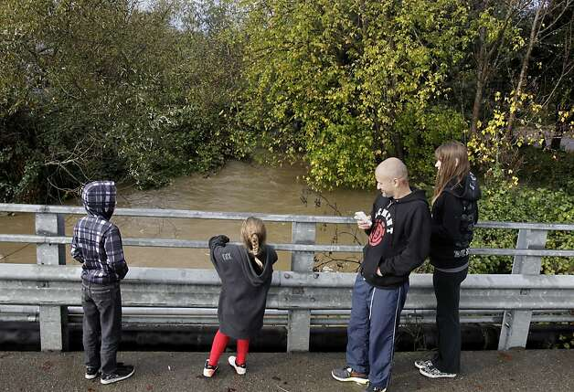 The Hildebrand and Martinez families watched Lichau Creek in Penngrove, Calif. (Sonoma County) rise to the highest level they have ever seen. The third of the big storms to hit the Bay Area this weekend dropped a lot of rain but thankfully failed to flood the major rivers including the Napa river Sunday December 2, 2012. Photo: Brant Ward, The Chronicle
