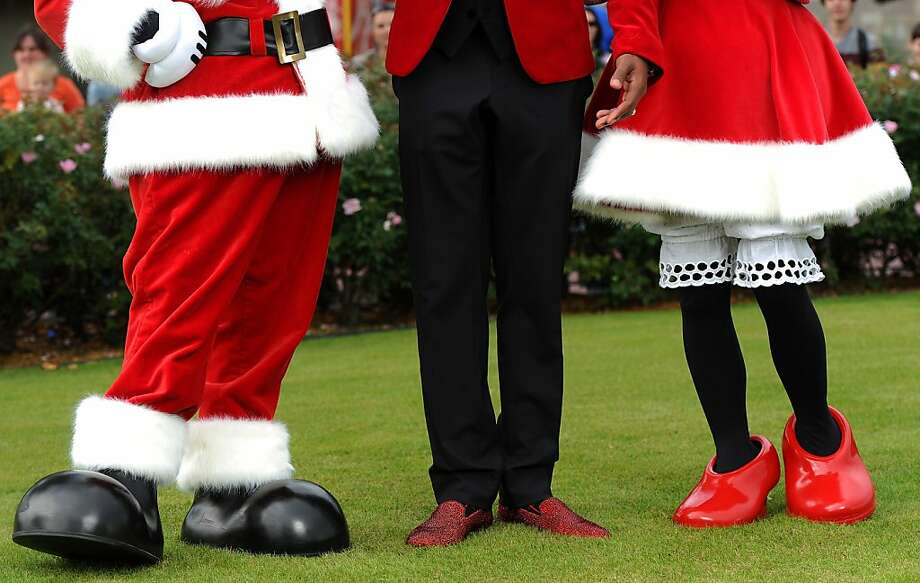 "Disney, close-up photo shows actor Nick Cannon's sparkling red holiday shoes (C) as he stands with Mickey Mouse (L) and Minnie Mouse (R) while taping the ""Disney Parks Christmas Day Parade"" TV special in the Magic Kingdom park at Walt Disney World on December 1,2012 in Lake Buena Vista, Florida.  Cannon is one of the hosts for the holiday special. The annual parade telecast, which airs Dec. 25, 2012 at various times across the country on ABC-TV, features celebrity performances and segments taped at Walt Disney World in Florida and Disneyland Resort in California.  Featured performers include Lady Antebellum, Backstreet Boys, Brad Paisley, Phillip Phillips, Colbie Caillat, TobyMac, Yolanda Adams, Ross Lynch, the cast of ""Newsies"" and a U.S. Marine Corps Band. (Photo by Mark Ashman/ Disney via Getty Images) Photo: Handout, Disney Via Getty Images"
