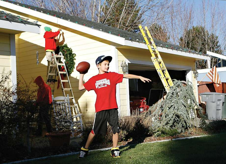 Joey Pearson, 8, plays in the front yard while Jesse Wiebe, top, and Jack Manis of Senske Lawn & Tree Care in Kennewick decorate his family's home in Richland, Wash., on Saturday, Dec. 1, 2012. His father Josh Pearson is a patient and volunteer at the Tri-Cities Cancer Center and the donated Christmas lights were a token of appreciation for Josh's work at the center. Senske also decorates the cancer center. (AP Photo/Tri-City Herald, Kai-Huei Yau) Photo: Kai-Huei Yau, Associated Press