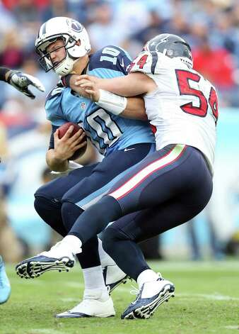 Titans QB Jake Locker (10) is sacked by the Texans' Barrett Ruud. Efforts like Ruud's helped Houston's defense force a franchise-record six turnovers. Photo: Andy Lyons, Getty Images / 2012 Getty Images