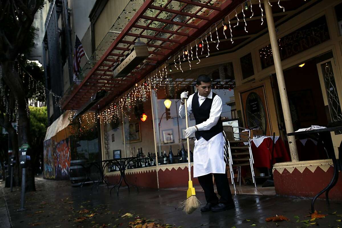 Nelvin Alvarez (cq) sweeps the sidewalk in front of Piazza Pelegrini, the restaurant next door to the boarded up Pagoda Theater at the intersection of Powell and Columbus in San Francisco, Calif., Sunday, December 2, 2012.