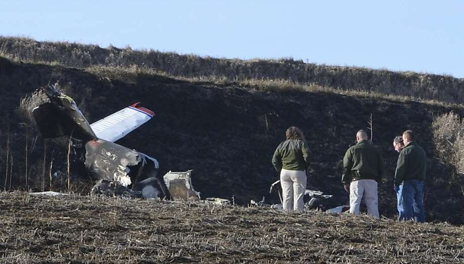 Officials investigate a plane crash near Correctionville, Iowa, Sunday, Dec. 2, 2012. The plane crashed Saturday evening, Dec. 1, 2012, injuring the pilot and killing two passengers. Authorities say Gaylen Knaack, of Correctionville, was flying the plane when it crashed into a farm field 2½ miles south of Correctionville around 8 p.m. (AP Photo/Sioux City Journal, Lauren Mills) Photo: Lauren Mills, Associated Press