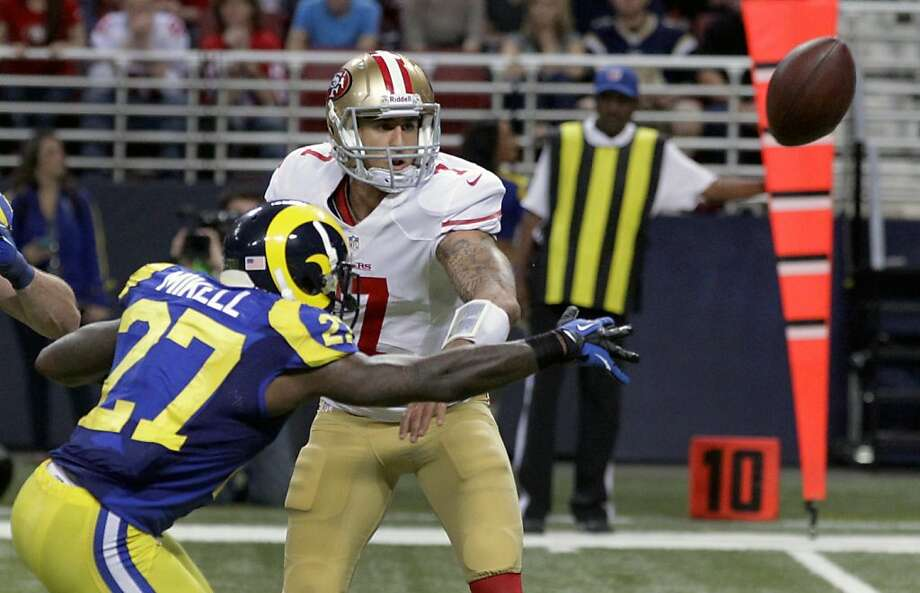 As Colin Kaepernick launches his ill-fated pitch, St. Louis safety Quintin Mikell (27) makes his job difficult. Photo: Seth Perlman, Associated Press