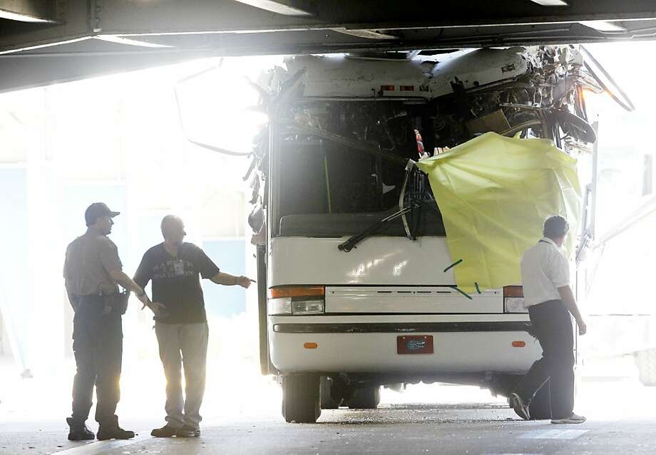 Law enforcement officers stand next to a bus after it hit a concrete overpass at Miami International Airport in Miami on Saturday, Dec. 1, 2012. The vehicle was too tall for the 8-foot-6-inch entrance to the arrivals area, and buses are supposed to go through the departures area which has a higher ceiling, according to an airport spokesperson. (AP Photo/Wilfredo Lee) Photo: Wilfredo Lee, Associated Press
