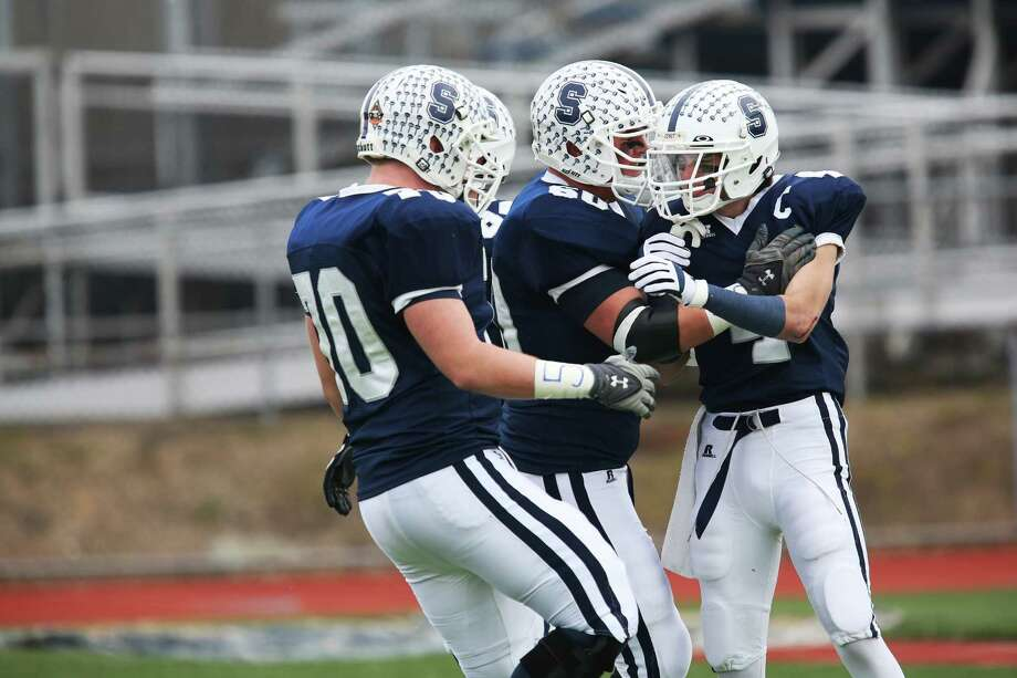 Mike Ross Connecticut Post freelance -Staples High School's #4 James Frusciante gets congraulated by teammates after scoring Staples first touchdown against Norwich Free Academy during Sunday Class LL football semifinals. NFA would win 30-28. Photo: Mike Ross / Connecticut Post Freelance