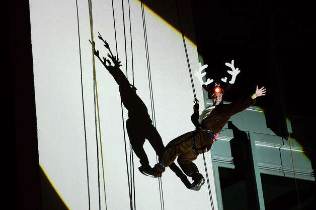 Rudolph rappels down the side of the Landmark Building in downtown Stamford, CT. He joined Bobby Valentine, Brian Cashman, Santa and Mrs. Claus in a holiday rappelling celebration on Dec. 2, 2012. Photo: Shelley Cryan / Shelley Cryan for the Stamford Advocate/ freelance Shelley Cryan