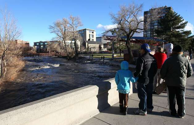 People come out to watch the surging Truckee River, in downtown Reno, Nev., on Sunday, Dec. 2, 2012, as a heavy, wet storm hit the Northern Nevada region. The storm delivered more snow and less rain than forecast, blunting the flood danger. (AP Photo/Cathleen Allison) Photo: Cathleen Allison, Associated Press