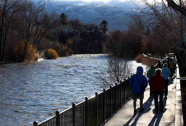Hundreds of people came out to watch the surging Truckee River, in downtown Reno, Nev., on Sunday, Dec. 2, 2012, as a heavy, wet storm hit the Northern Nevada region. The storm delivered more snow and less rain than forecast, blunting the flood danger. (AP Photo/Cathleen Allison) Photo: Cathleen Allison, Associated Press
