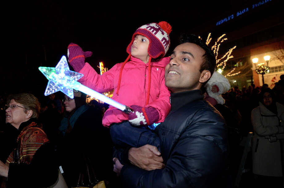 Haseem and his daughter Azita, 2, Stamford, who declined to give a last name, enjoy a holiday show in Latham park after a rappelling celebration where Santa, Rudolph, Brian Cashman, Bobby Valentine and friends had dropped down the side of the Landmark Building in downtown Stamford, CT on Dec. 2, 2012. Photo: Shelley Cryan / Shelley Cryan for the Stamford Advocate/ freelance Shelley Cryan