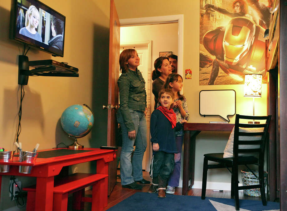 Daniel Adair, 6 (center front), and his sister Sarah McCreight, 14 (from left); mom Mary Adair; dad Keith Adair (background); and sister Katherine Adair, 8, react as they see Daniel's bedroom, which was redecorated by the Wish Connection. Photo: Edward A. Ornelas, San Antonio Express-News / © 2012 San Antonio Express-News