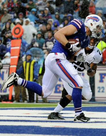 Buffalo Bills tight end Scott Chandler (84) catches a touchdown pass in front of Jacksonville Jaguars' Dwight Lowery (25) during the first half of an NFL football game on Sunday, Dec. 2, 2012 in Orchard Park, N.Y. (AP Photo/Gary Wiepert) Photo: Gary Wiepert