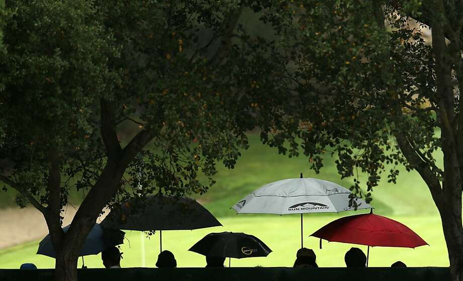 Members of the gallery hold umbrellas in the stands around the ninth green during the final round of the Tiger Woods World Challenge Presented by Northwestern Mutual at Sherwood Country Club on December 2, 2012 in Thousand Oaks, California.  (Photo by Stephen Dunn/Getty Images) Photo: Stephen Dunn, Getty Images