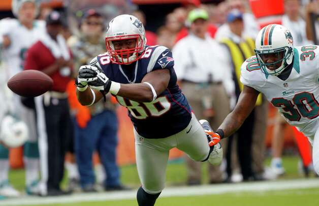 New England Patriots tight end Daniel Fells (86) cannot hold on to a pass as Miami Dolphins strong safety Chris Clemons (30) defends during the first half of an NFL football game on Sunday, Dec. 2, 2012, in Miami. (AP Photo/John Bazemore) Photo: John Bazemore