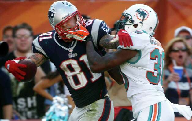 Miami Dolphins strong safety Chris Clemons (30) grabs New England Patriots tight end Aaron Hernandez (81) face mask during the second half of an NFL football game on Sunday, Dec. 2, 2012, in Miami. (AP Photo/John Bazemore) Photo: John Bazemore