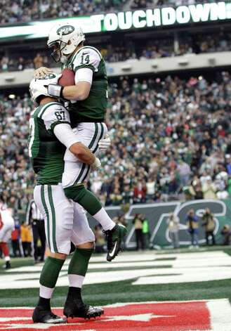 New York Jets quarterback Greg McElroy (14) is lifted by teammate Konrad Reuland after throwing a 1-yard touchdown pass to tight end Jeff Cumberland during the second half of an NFL football game against the Arizona Cardinals, Sunday, Dec. 2, 2012, in East Rutherford, N.J. (AP Photo/Kathy Willens) Photo: Kathy Willens
