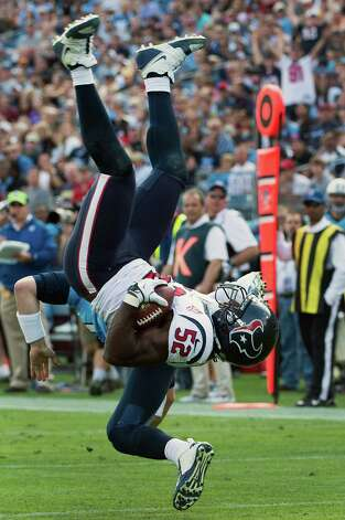 While attempting to return an interception for a touchdown, Texans linebacker Tim Dobbins is upended by Titans quarterback Jake Locker. Photo: Smiley N. Pool, Houston Chronicle / © 2012  Houston Chronicle