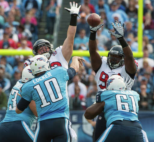 Texans defensive lineman Earl Mitchell deflects an attempted pass by Titans quarterback Jake Locker. Photo: Smiley N. Pool, Houston Chronicle / © 2012  Houston Chronicle