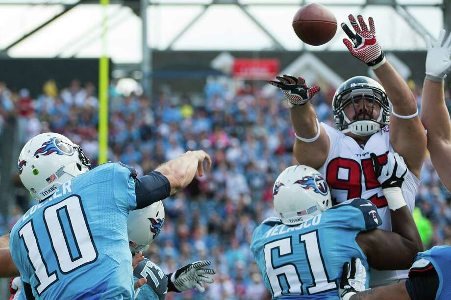 Texans defensive lineman Shaun Cody gets his hands on a pass from Titans quarterback Jake Locker. Photo: Smiley N. Pool, Houston Chronicle / © 2012  Houston Chronicle