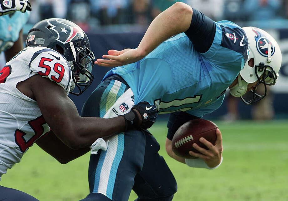 Titans quarterback Jake Locker is sacked by Texans linebacker Whitney Mercilus. Photo: Smiley N. Pool, Houston Chronicle / © 2012  Houston Chronicle