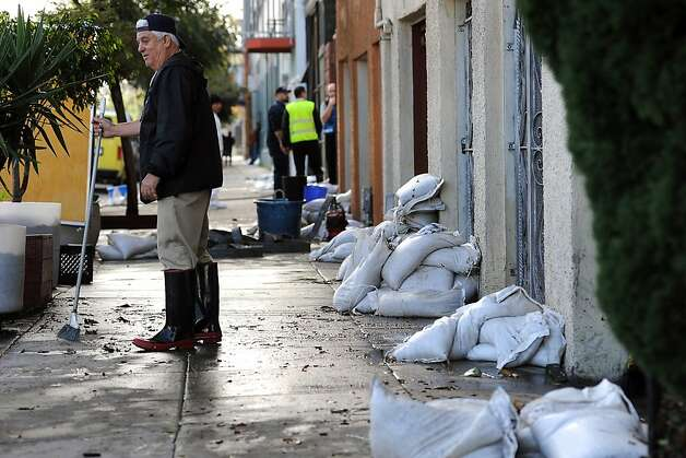 Building manager Sam Piccazo stands in front of his building where sand bags were put in place to block some of the flooding that inundated buildings on Folsom St.  Business on the 2100 block of Folsom St. in San Francisco were flooded this morning by water that backed up through the sewage lines.  Sunday December 2nd, 2012. Photo: Michael Short, Special To The Chronicle